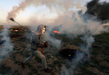 A Palestinian demonstrator uses a sling to hurl back a tear gas canister fired by Israeli troops