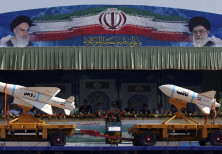 A military vehicle carrying Iranian Zoobin smart bomb (L) and Sagheb missile under pictures of Iran'