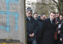 Emmanuel Macron looks at a grave defaced with a swastika during a visit to the Jewish cemetery
