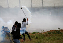 A Palestinian demonstrator uses a sling to hurl back a tear gas canister fired by Israeli forces dur