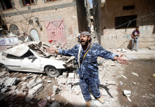 A Houthi security officer reacts at the site of an air strike launched by the Saudi-led coalition in