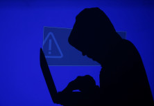 Hooded man holds laptop computer as blue screen with an exclamation mark is projected on him