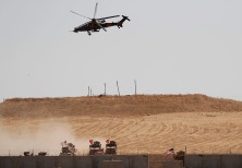 A Turkish military helicopter flies over as Turkish and U.S. troops return from a joint U.S.-Turkey