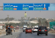 Cars pass under a road sign that shows the direction to Manbij city, at the entrance of Manbij, Syri
