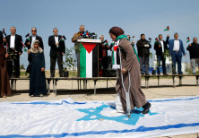 A Palestinian woman steps on a replica of an Israeli flag during an event marking Land Day near the