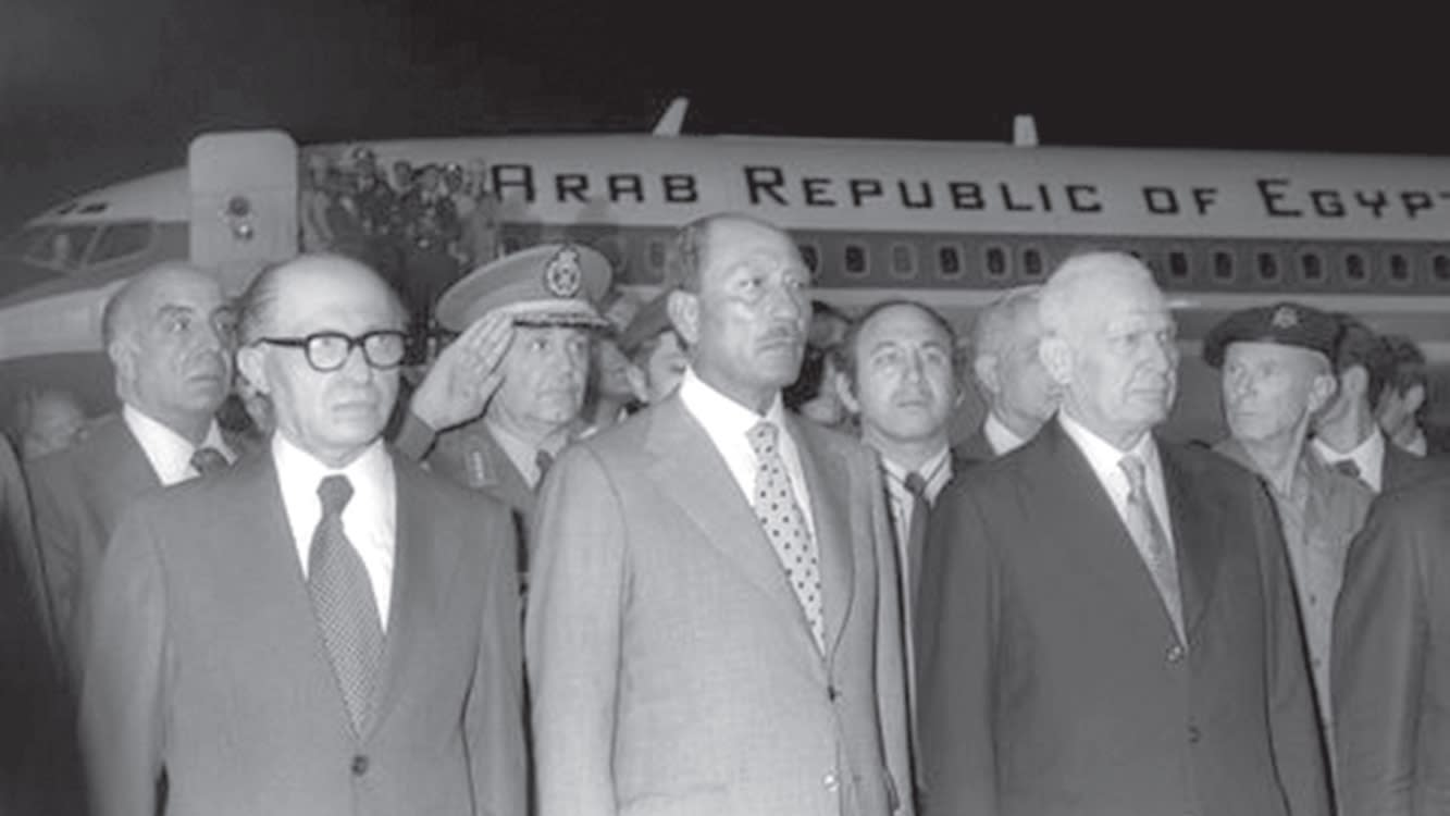 Egyptian President Anwar Sadat and Israeli Prime Minister Menachem Begin stand together at Ben Gurion Airport after Sadat's arrival on November 19, 1977. (GPO)