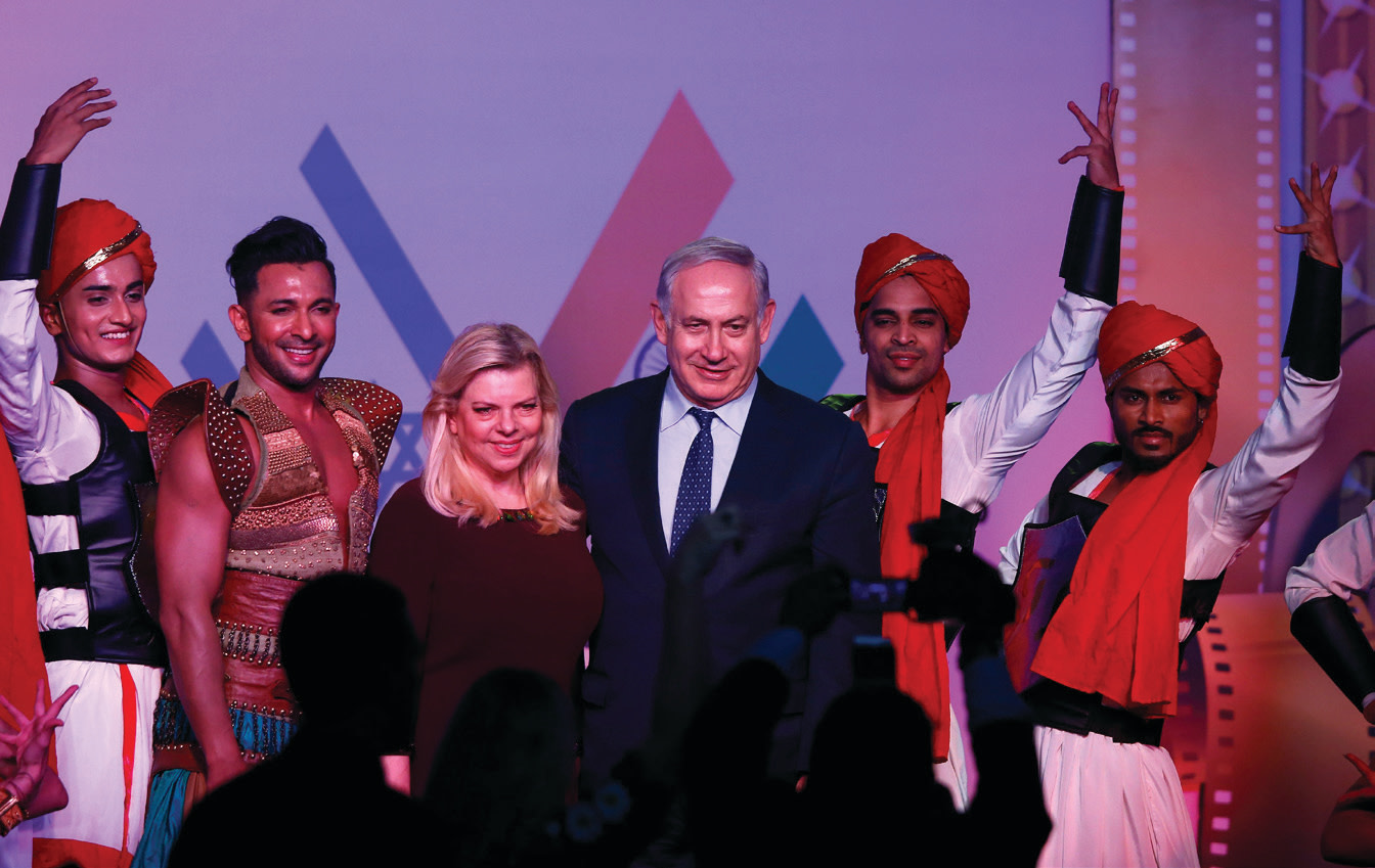 PRIME MINISTER Benjamin Netanyahu and his wife, Sara, pose with dancers during 'Shalom Bollywood' event in Mumbai, India in January 2018 (SHAILESH ANDRADE/REUTERS)