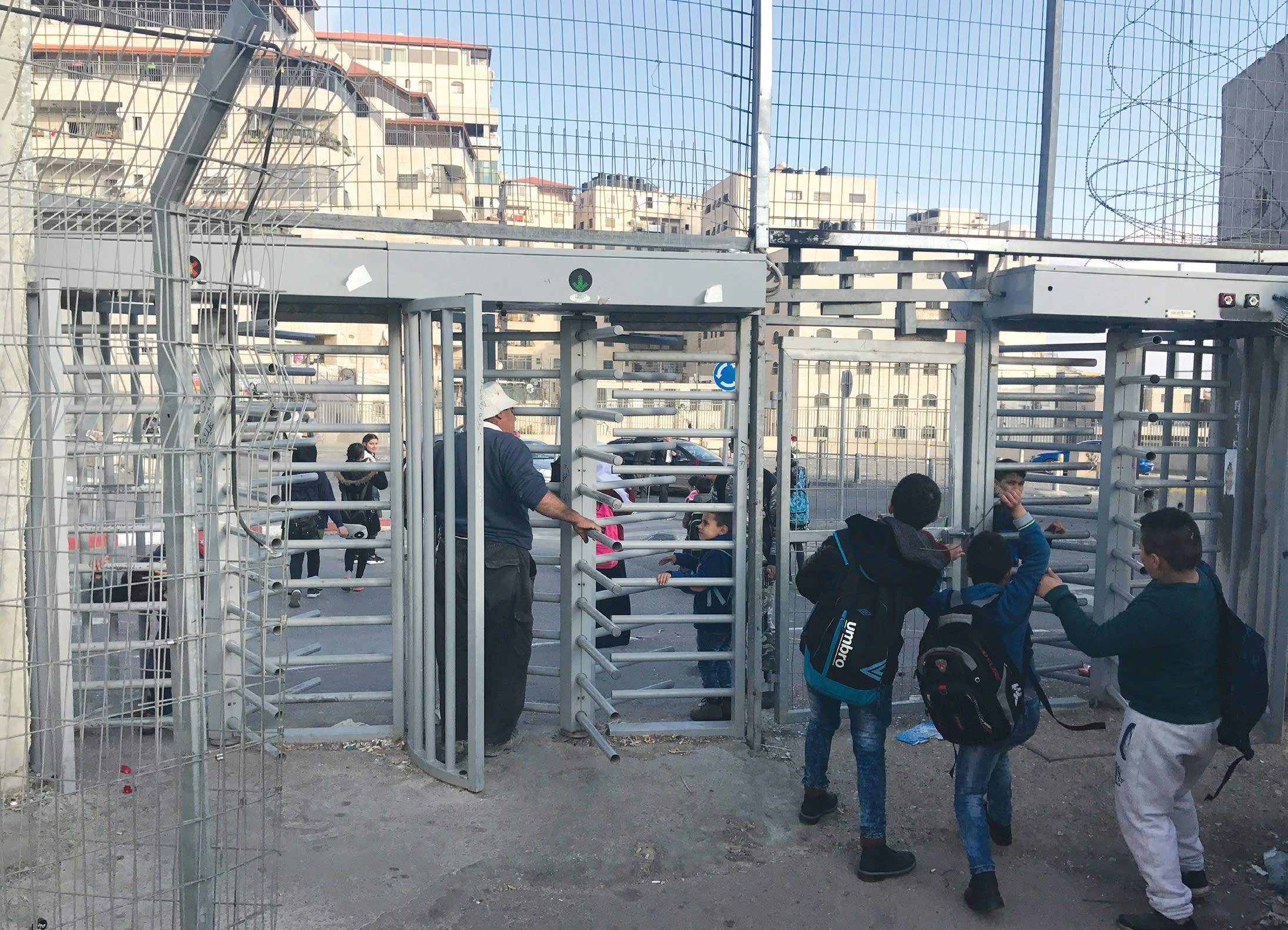 CHILDREN HEAD through revolving metal gates this month, to enter a walled-off section of Jerusalem that incorporates the Shuafat refugee camp. (Udi Shaham)