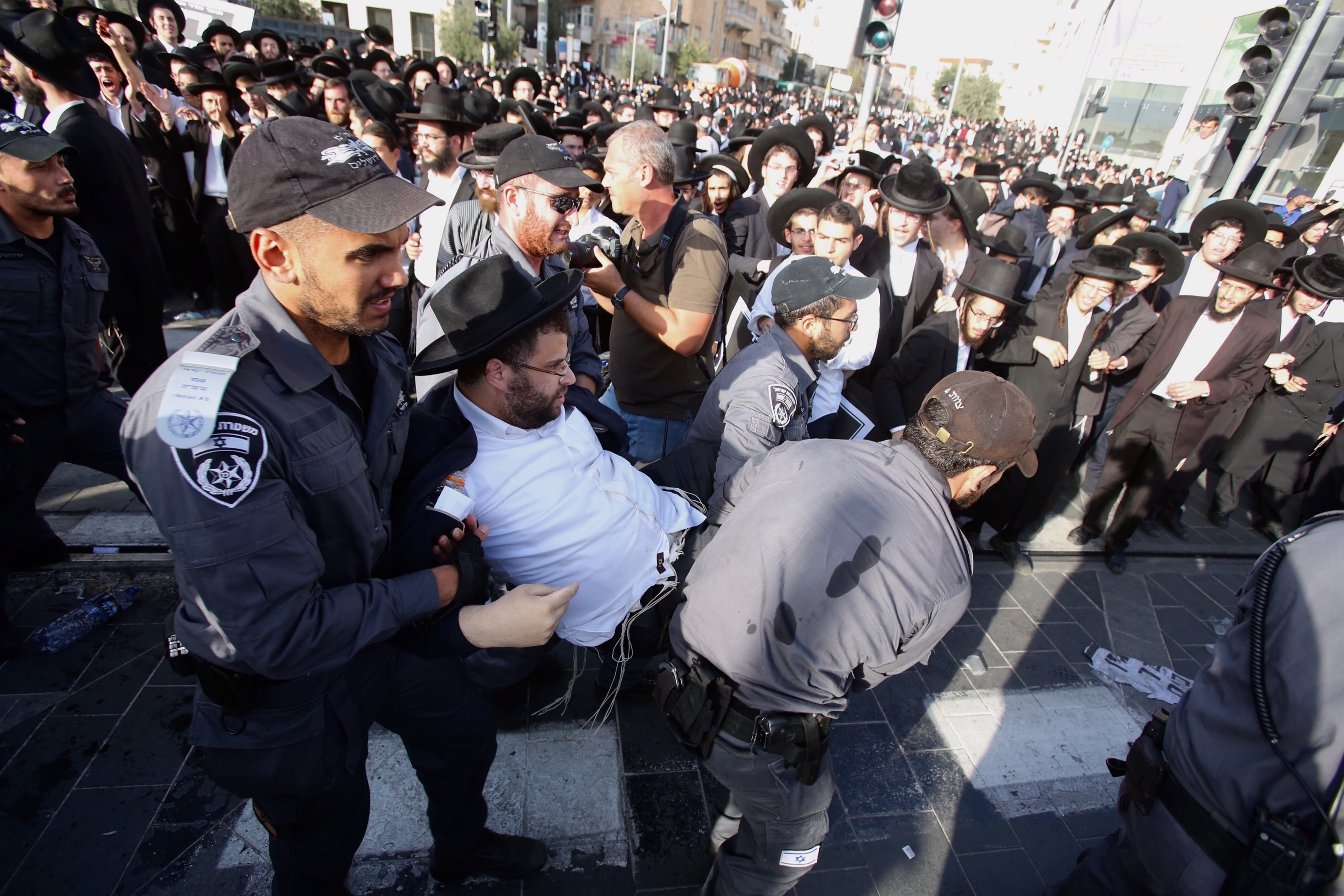 Police arrest a haredi man protesting against the drafting of ultra-Orthodox into the IDF, October 2017 (MARC ISRAEL SELLEM/THE JERUSALEM POST)