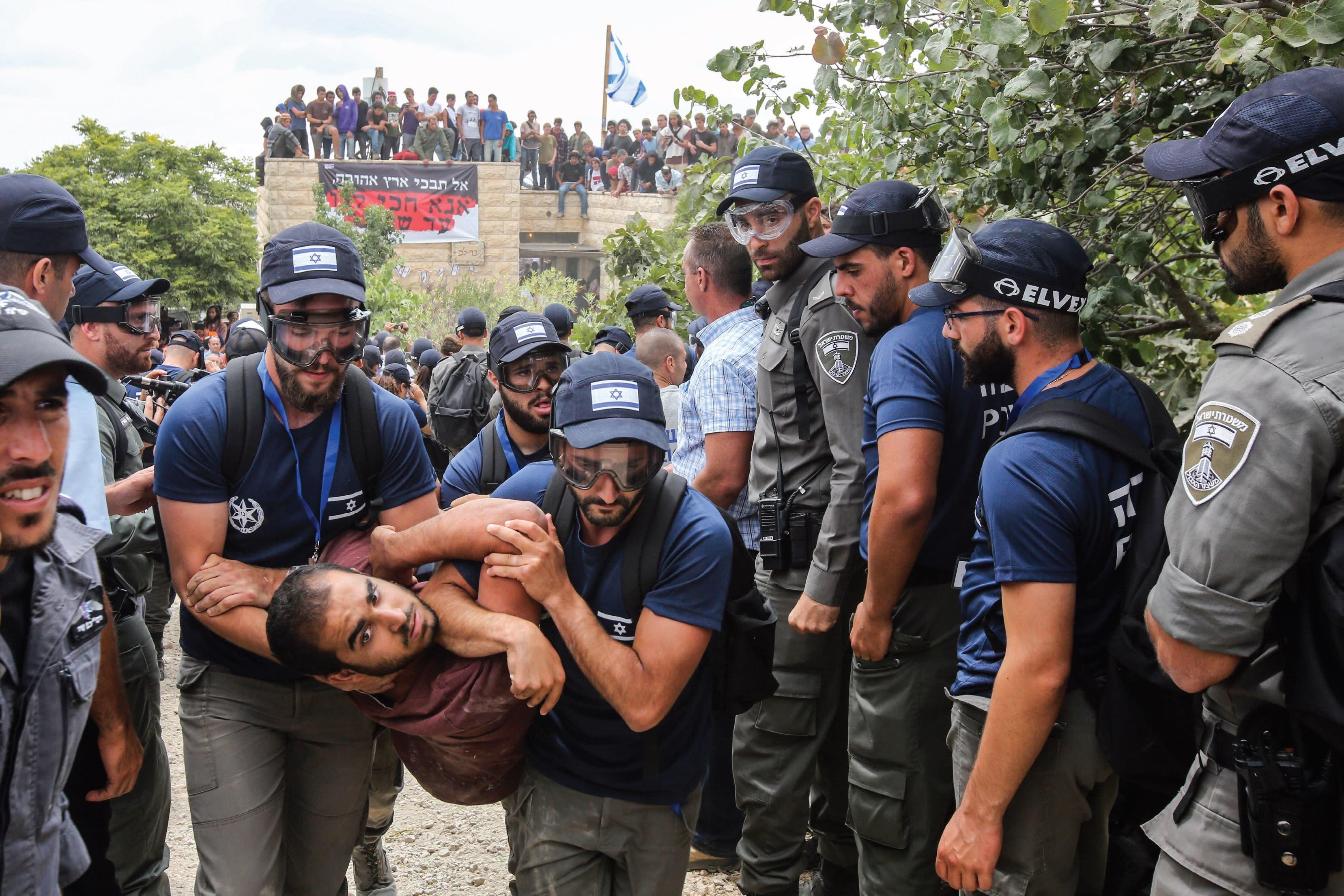 Security forces evict a demonstrator from Netiv Ha'avot, June 12, 2018 (Marc Israel Sellem)