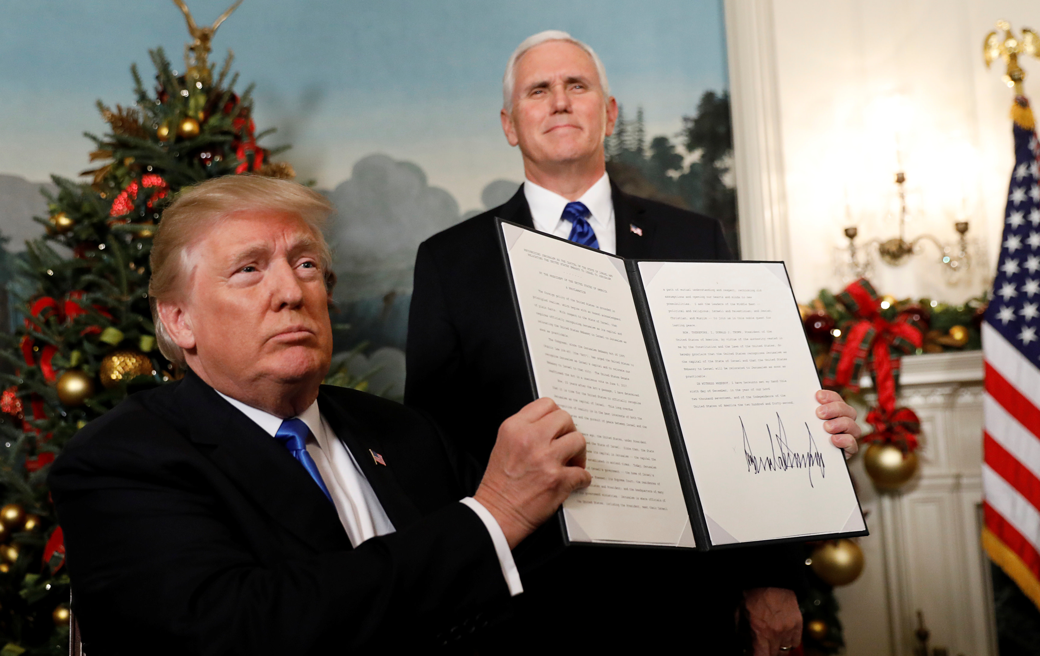 US President Donald Trump holds up the proclamation that the United States recognizes Jerusalem as the capital of Israel and will move its embassy there, December 6, 2017 (Reuters)