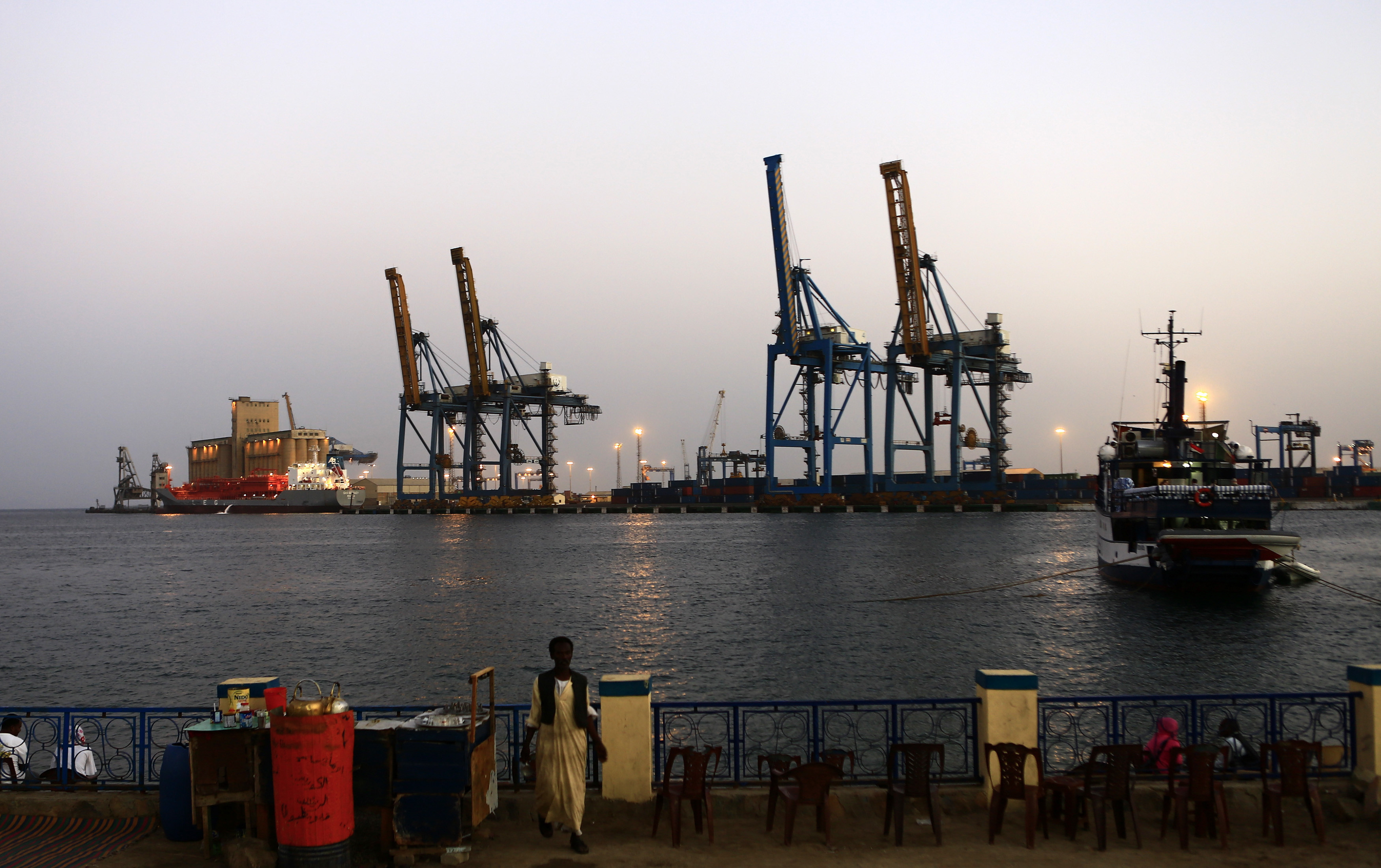 A man stands opposite the modern port at the harbour in Port Sudan, February 24, 2014. (Reuters)