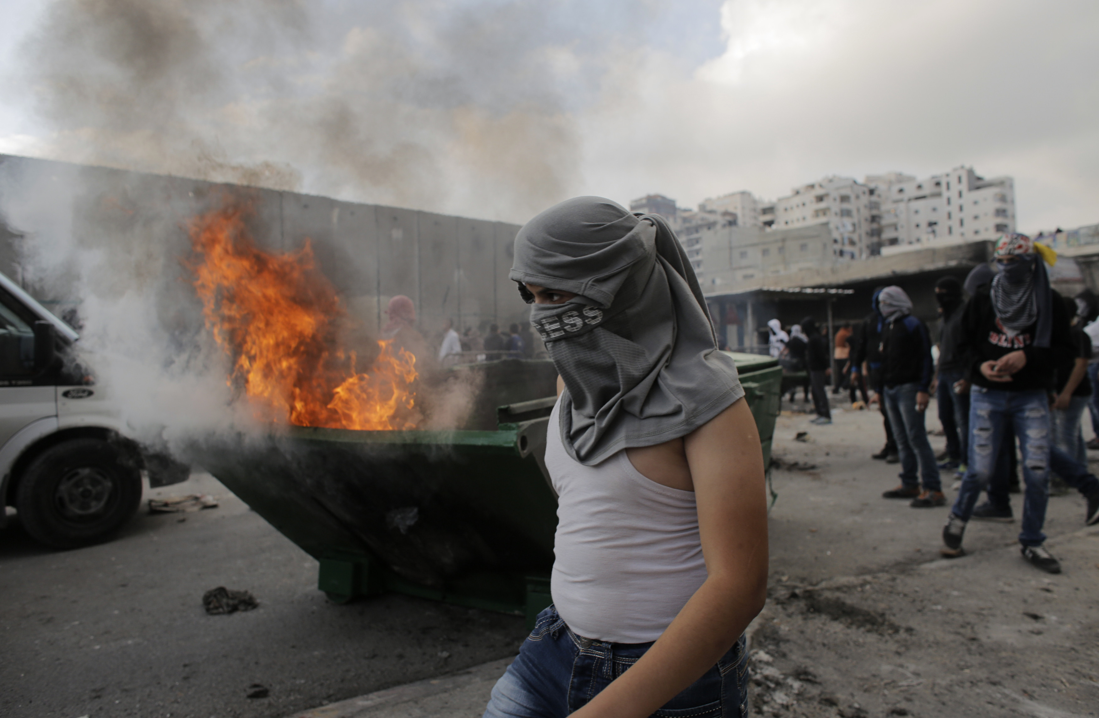 A Palestinian stone-thrower stands in front of garbage set ablaze during clashes with Israeli police on the outskirts of Jerusalem near Shuafat refugee camp November 5, 2014. (Reuters)