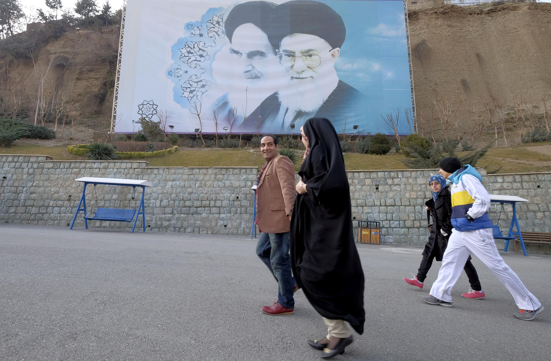 Iranians walk past a large picture of Iran's late leader Ayatollah Ruhollah Khomeini (L), and Iran's Supreme Leader Ayatollah Ali Khamenei at a park in Tehran, Iran, January 17, 2016 (Credit: RAHEB HOMAVANDI/TIMA VIA REUTERS)