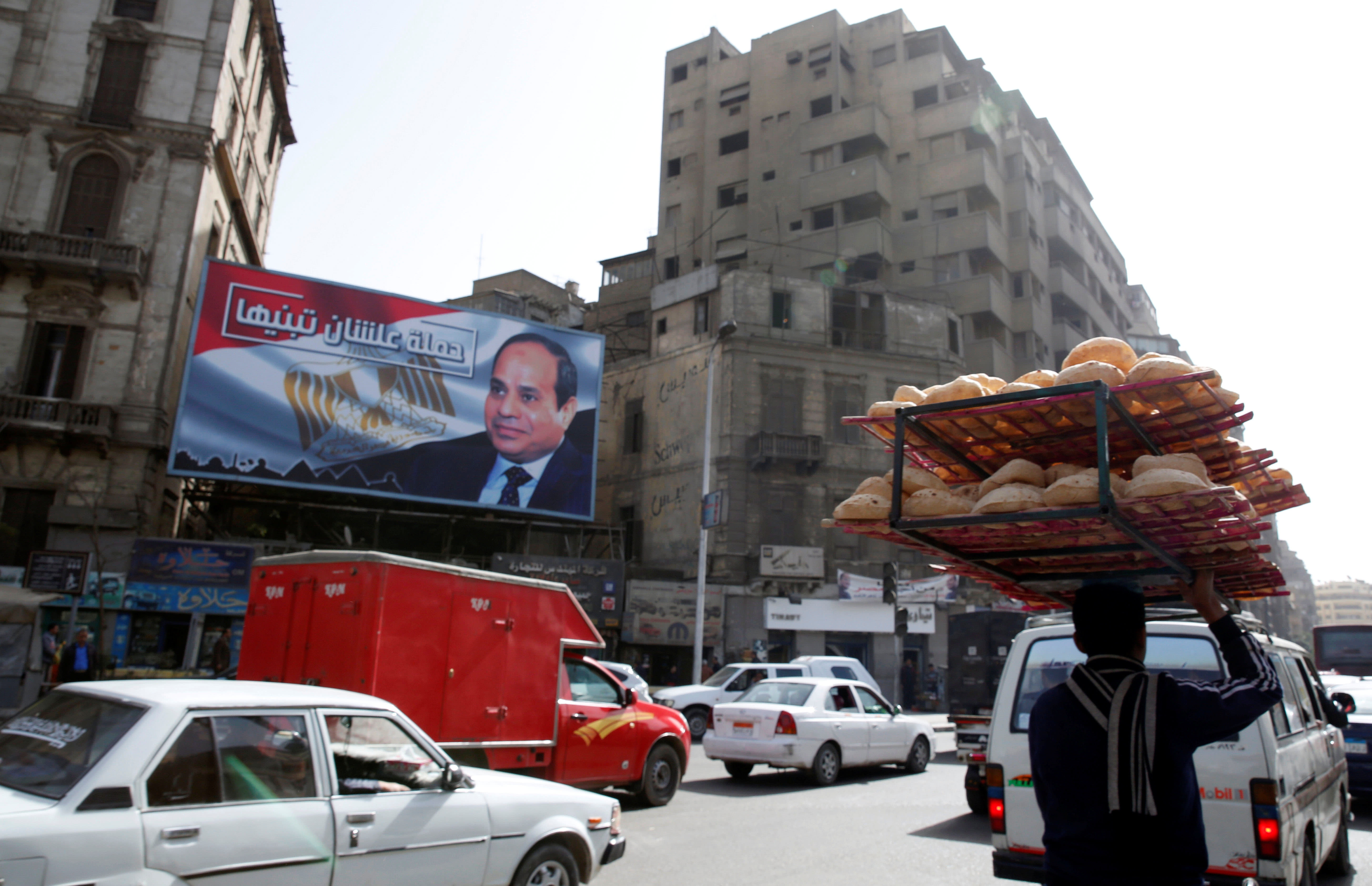 A busy street near a poster of Egypt's President Abdel Fattah al-Sisi for the upcoming presidential election in Cairo, Egypt, January 22, 2018 (Reuters)