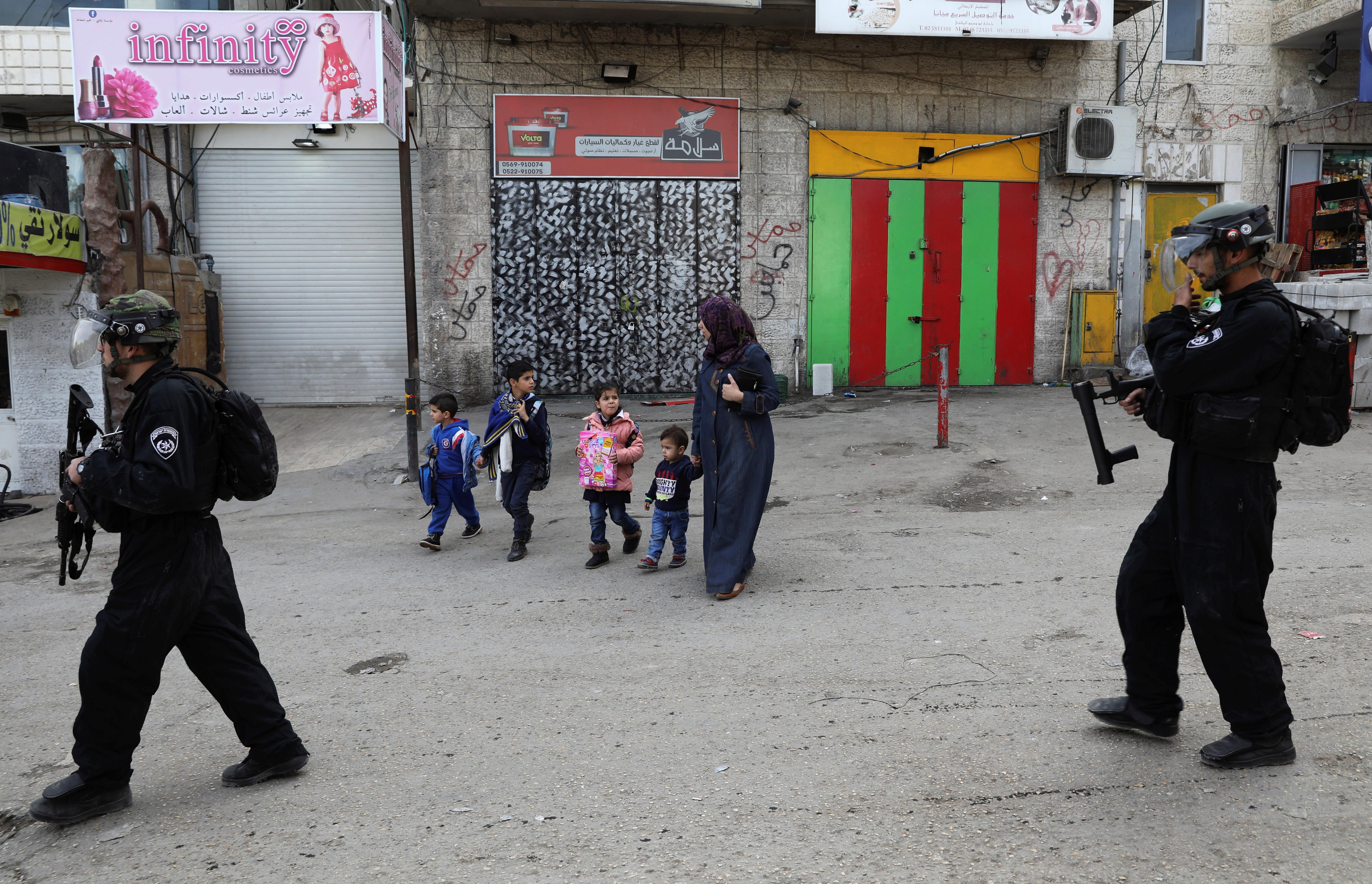 Israeli policemen patrol a street in the East Jerusalem refugee camp of Shuafat (Reuters)