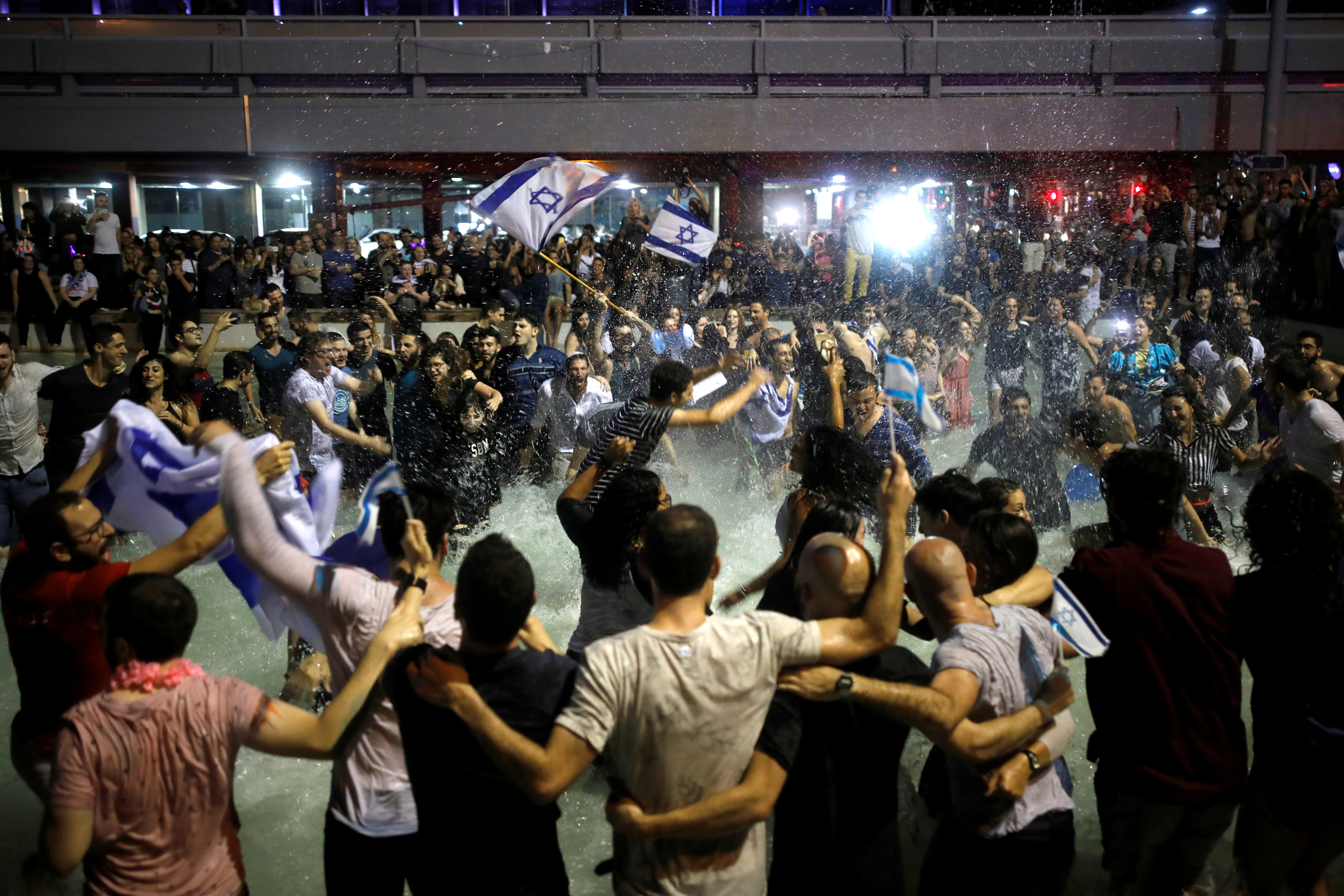 Israeli fans celebrate at Rabin square in Tel Aviv Israel, after Israeli singer Netta Barzilai won the Grand Final of Eurovision Song Contest 2018, May 13, 2018. (Reuters/Corinna Kern)