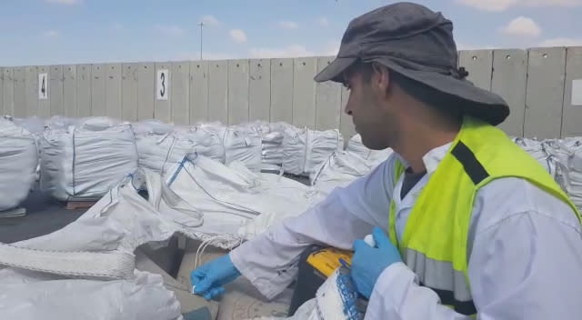 A security inspector checks materials destined for Gaza at Kerem Shalom Crossing (Defense Ministry)