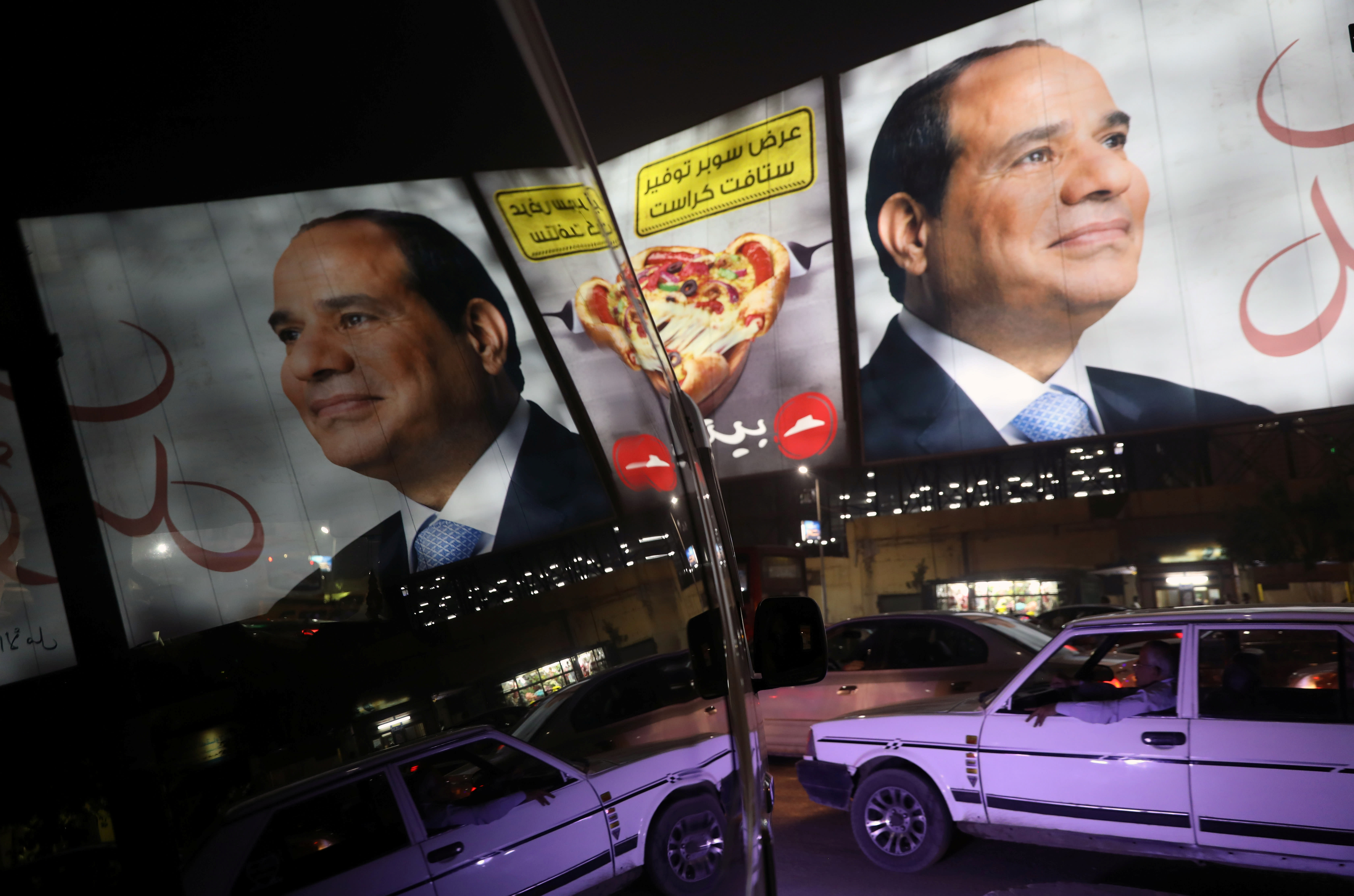 People walk in front of banners with Egypt's President Abdel Fattah al-Sisi during preparations for the presidential election in Cairo, Egypt (AMMAR AWAD/REUTERS)