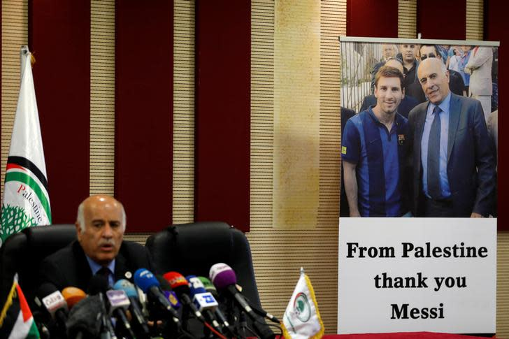 A poster of Palestinian FA chief Jibril Rajoub with Argentina's soccer player Lionel Messi is seen during Rajoub's news conference, in Ramallah in the West Bank June 6, 2018. (Reuters)