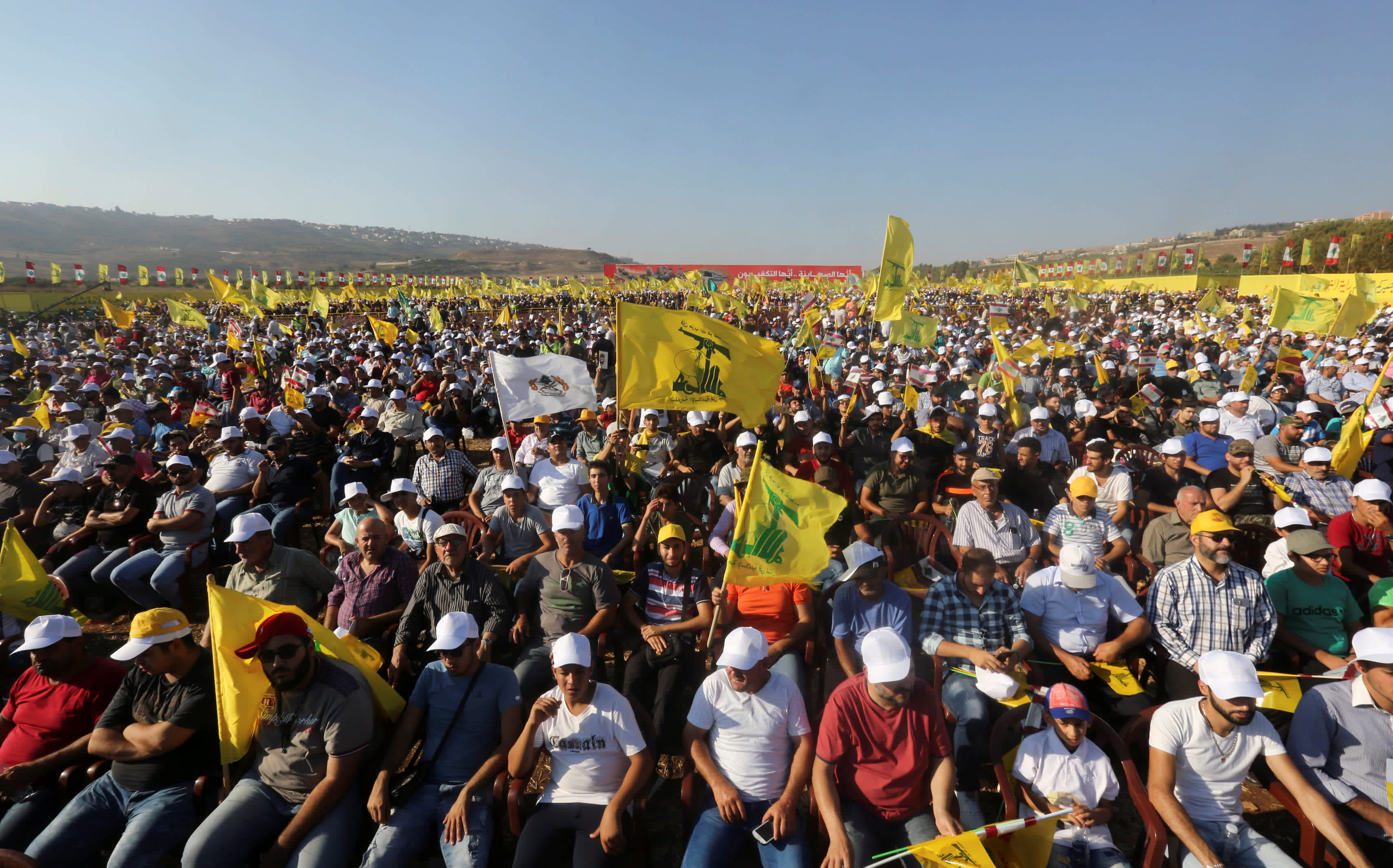 Supporters of Lebanon's Hezbollah leader Sayyed Hassan Nasrallah display Hezbollah flags during a rally marking the 11th anniversary of the end of Hezbollah's 2006 war with Israel, in the southern village of Khiam, Lebanon, August 13, 2017.  (Reuters/Aziz Taher)