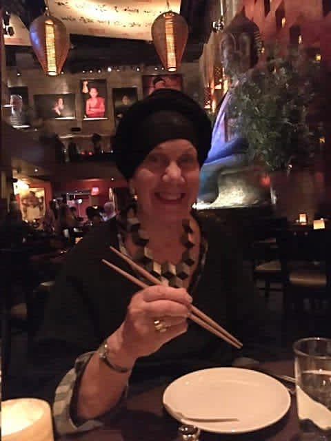 Rabbi Yocheved Mintz after procedure enjoying dinner with chopsticks (AMERICAN FRIENDS OF RAMBAM)