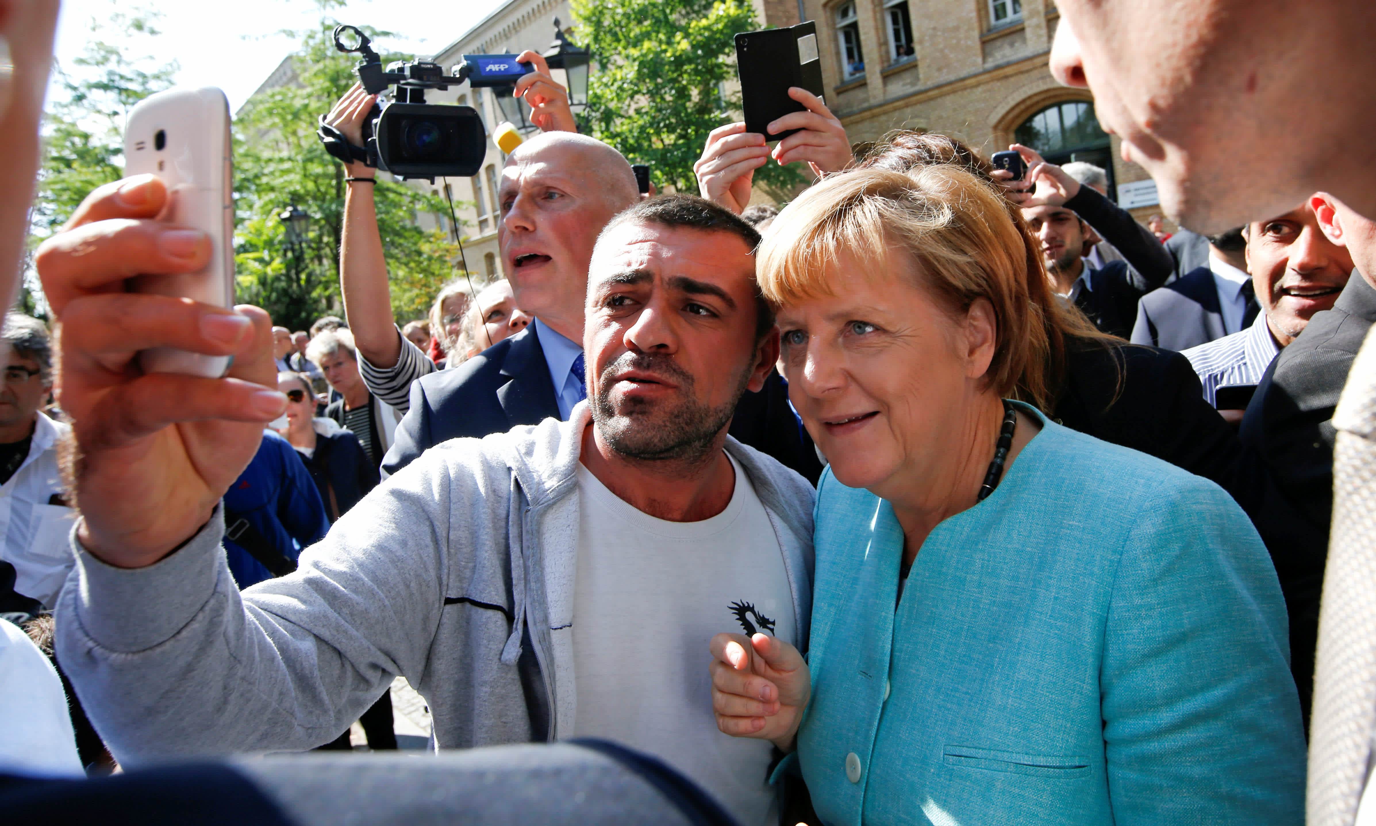 A migrant takes a selfie with German Chancellor Angela Merkel outside a refugee camp near the Federal Office for Migration and Refugees after registration at Berlin's Spandau district, Germany September 10, 2015 (REUTERS/FABRIZIO BENSCH)