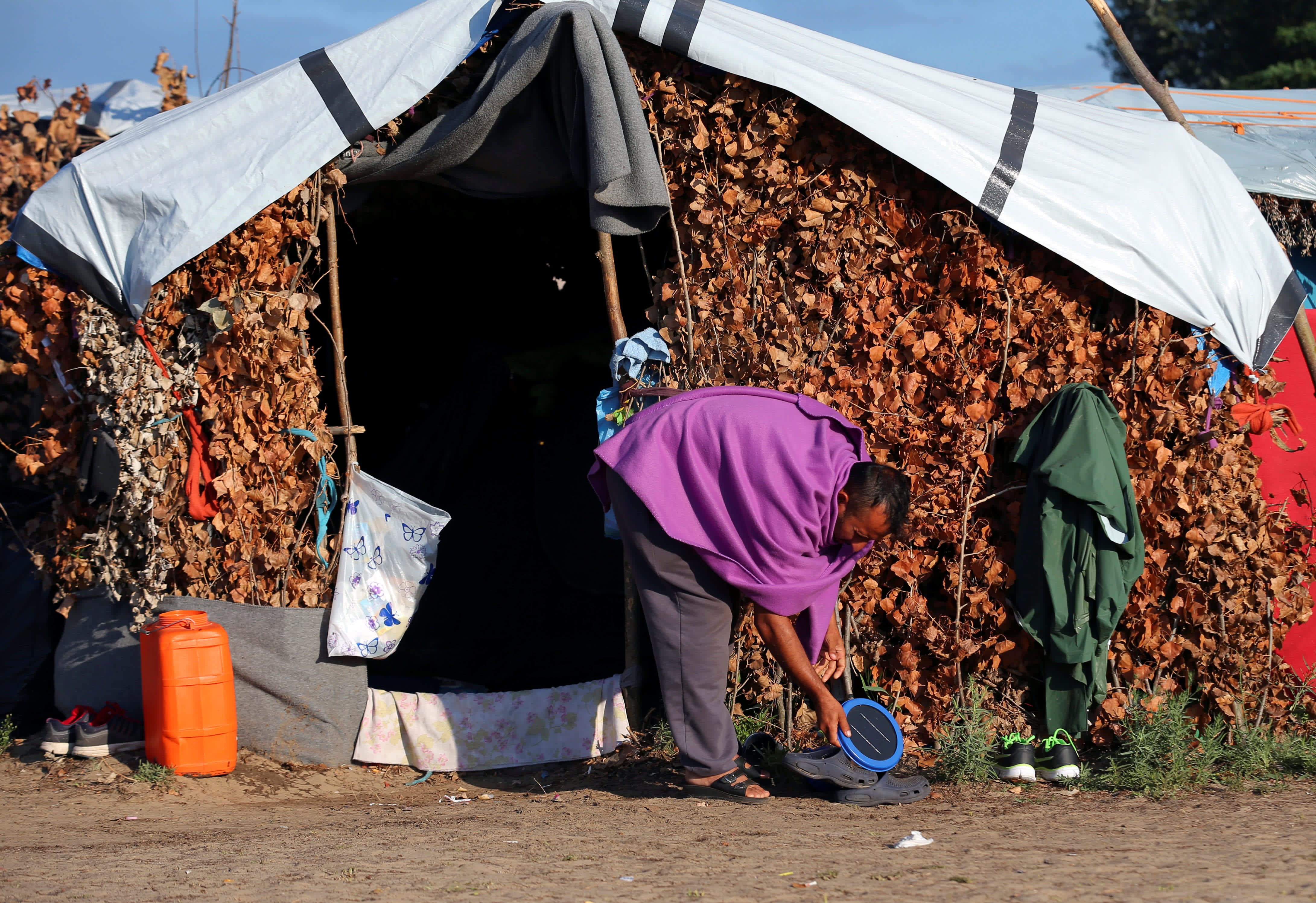 A refugee cleans his tent in a makeshift camp on the Hungary-Serbia border, on the Serbian side of a transit zone set up by Hungarian authorities to filter refugees at Roszke, Hungary, September 2, 2016 (REUTERS/LASZLO BALOGH)