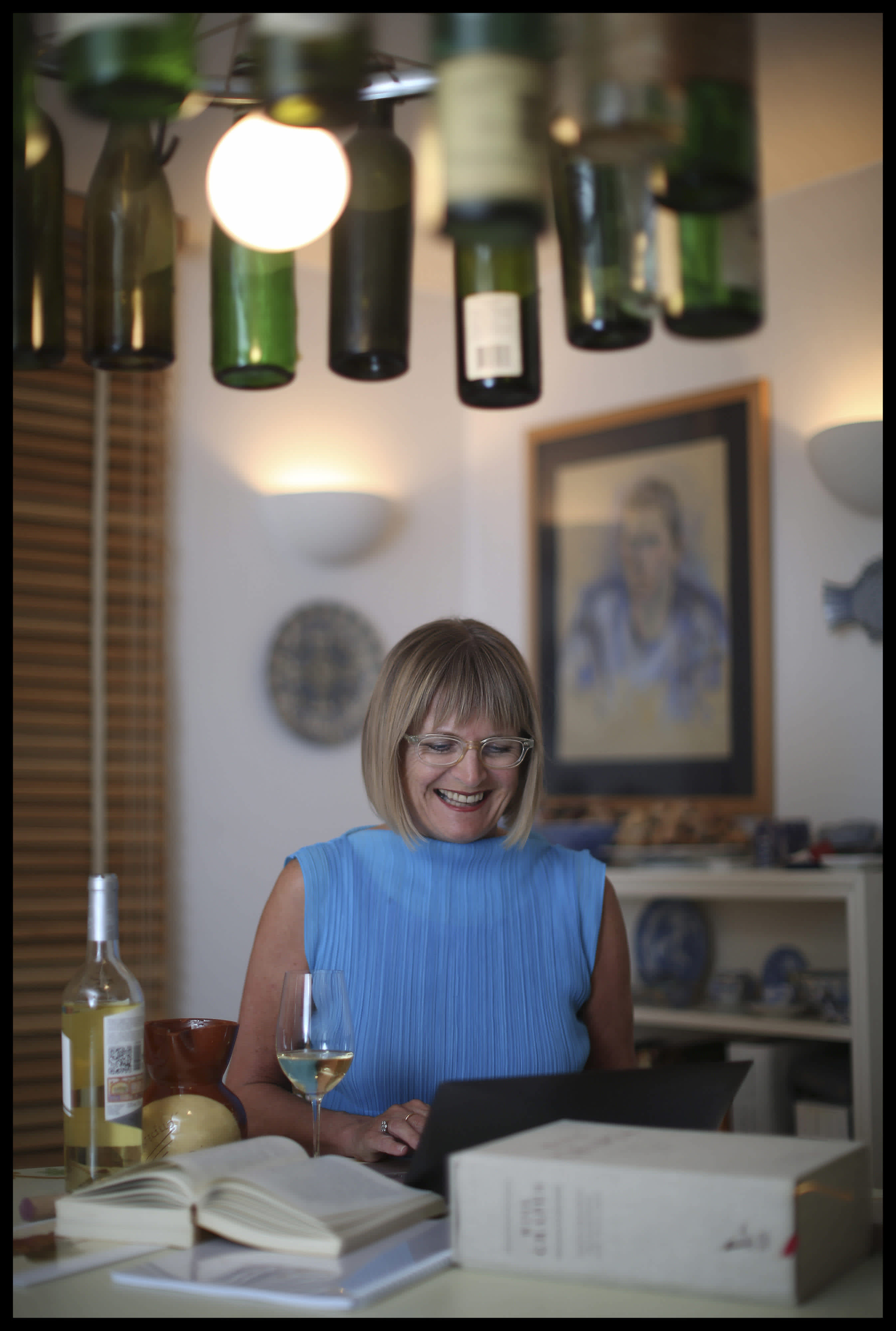 ancis Robinson at her laptop surrounding by wine bottles (courtesy)
