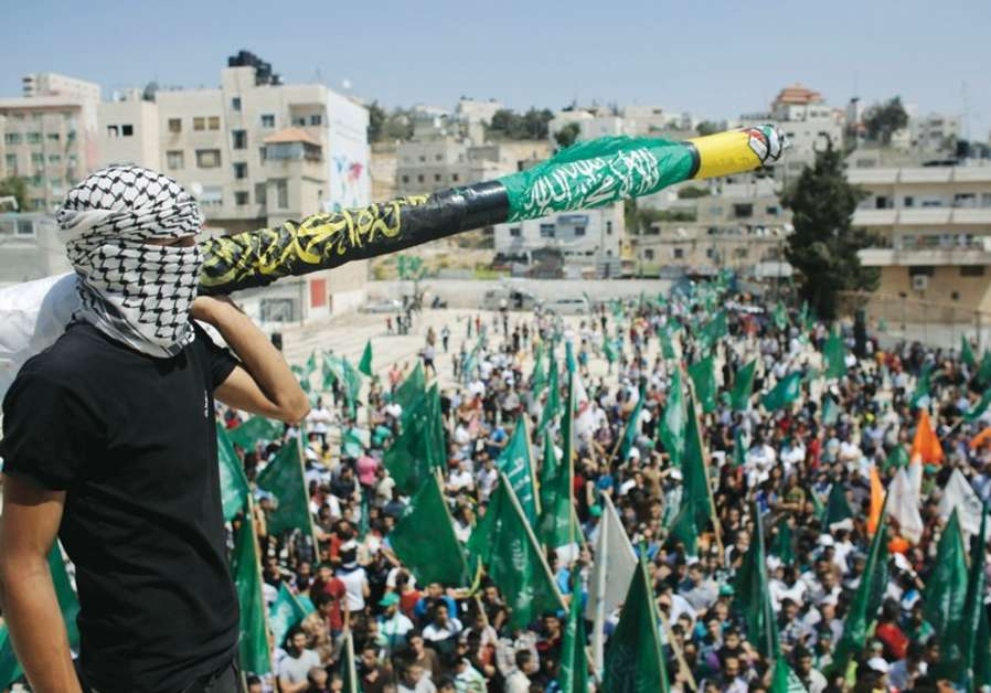 A MASKED Hamas supporter holds a mock missile at a Gaza celebration after last week's cease-fire. (photo credit:REUTERS