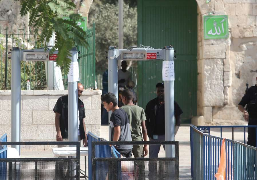 Israeli border police officers stand guard as Palestinians pray at Lions' Gate, the entrance to Jerusalem's Old City, in protest over Israel's new security measures at the Temple Mount July 20, 2017.