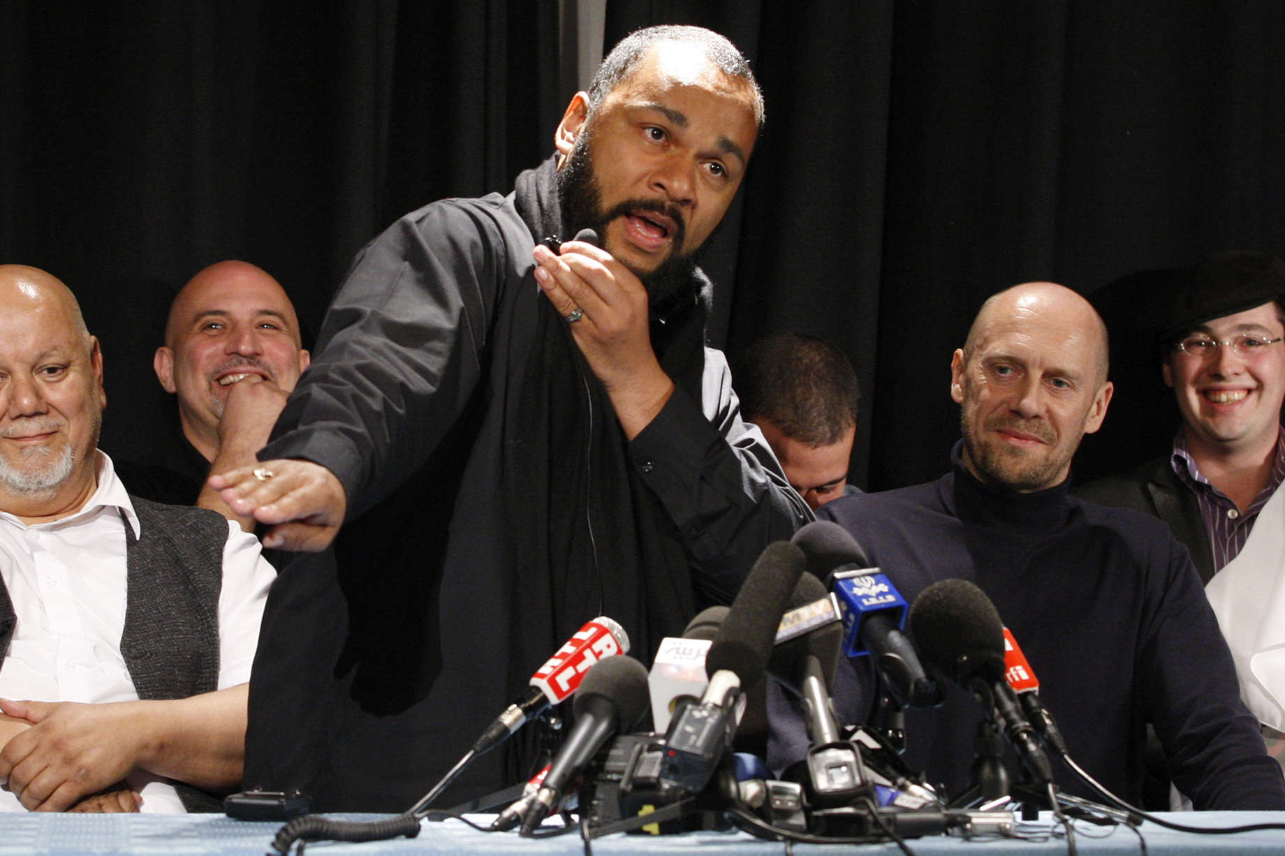 "French comedian Dieudonné (C) performs the ""quenelle"" gesture at a press conference (Reuters)"