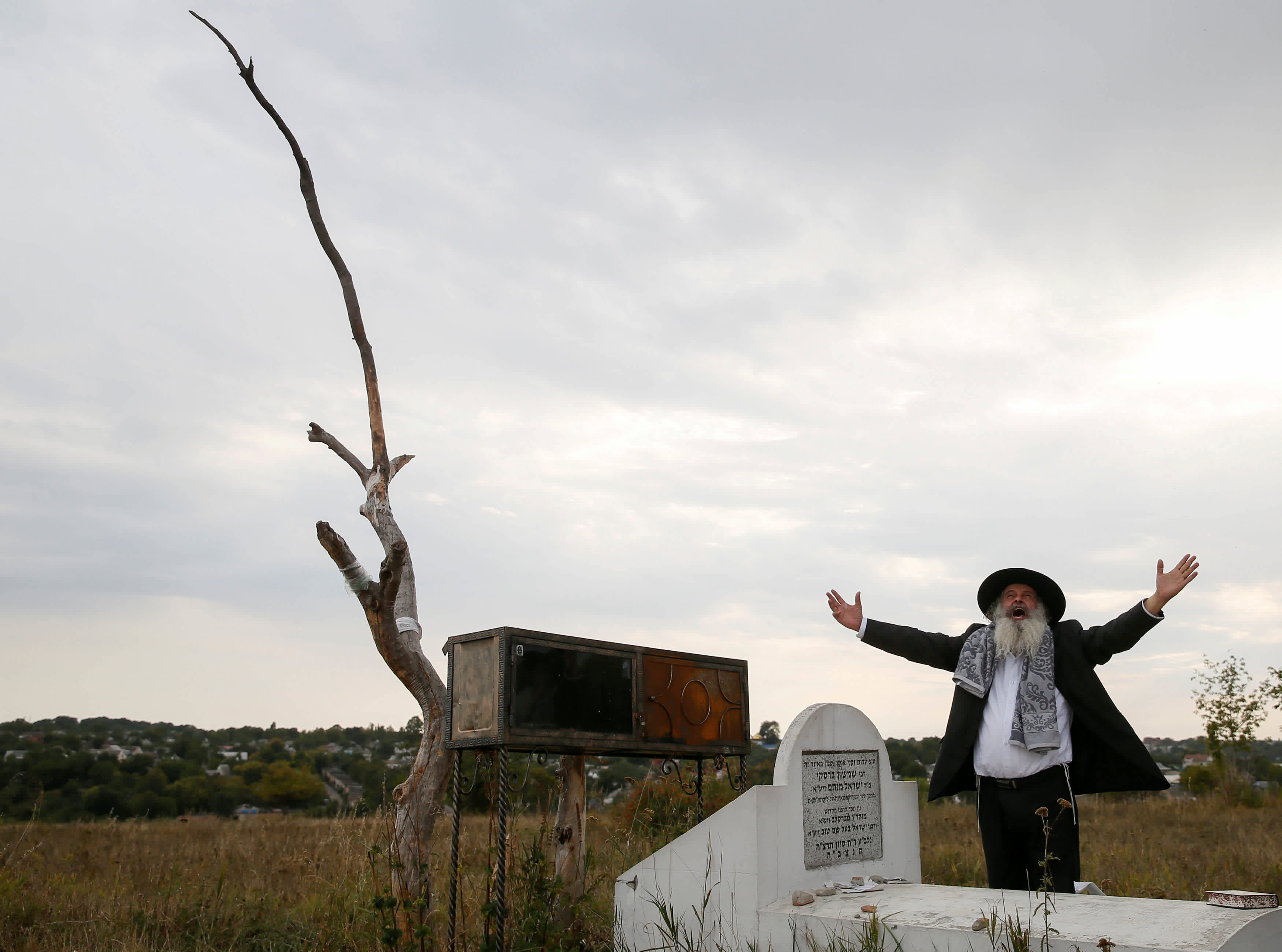 An ultra-Orthodox Jewish pilgrim prays next to a tomb at an old Jewish cemetery on the eve of Rosh Hashana holiday, the Jewish New Year, in the town of Uman, Ukraine September 19, 2017. (Reuters)