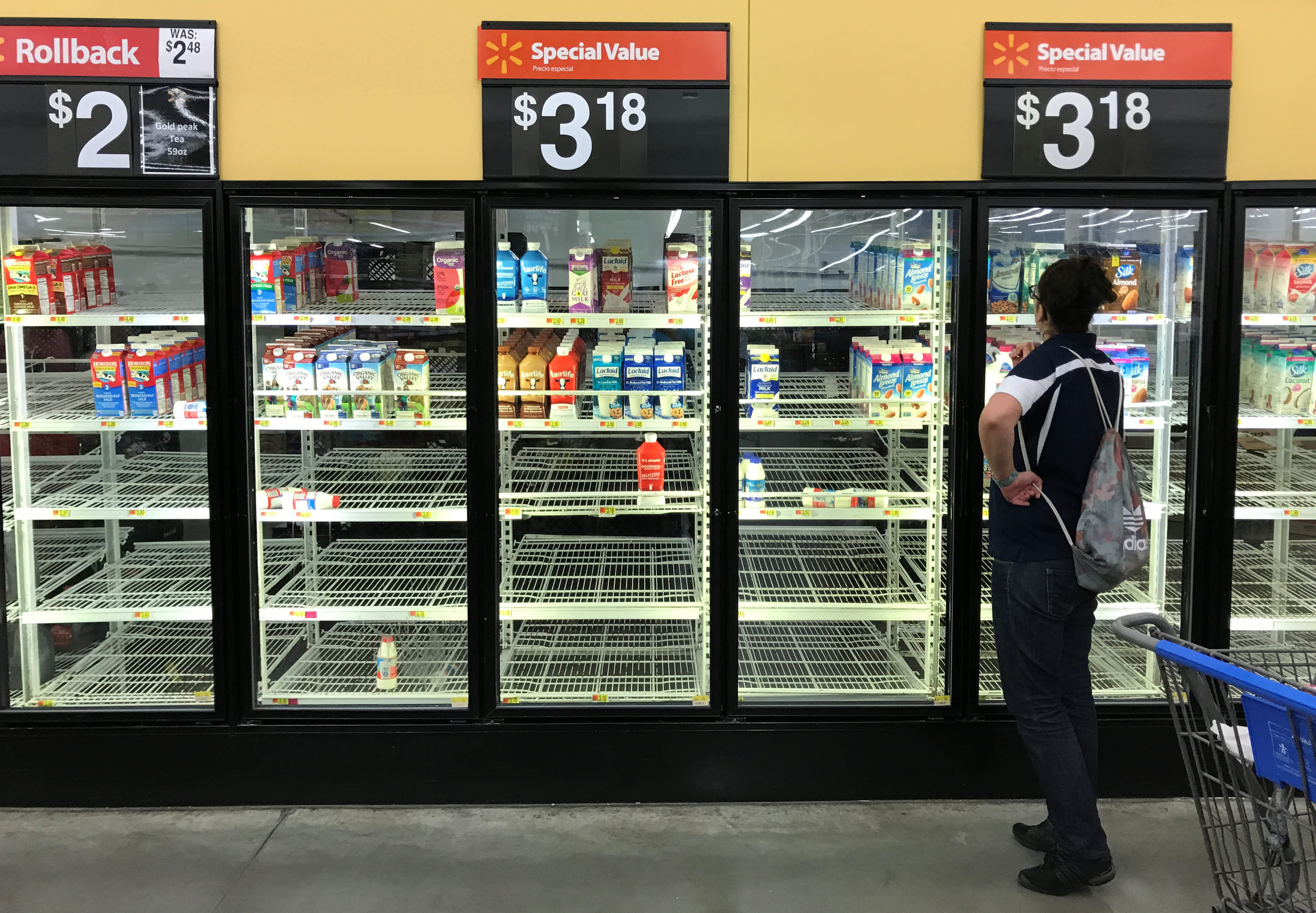 A woman looks over bare refrigerator shelves in a Walmart store in Houston, Texas, US, as Hurricane Harvey approaches landfall near the Texas coastal area, August 25, 2017.