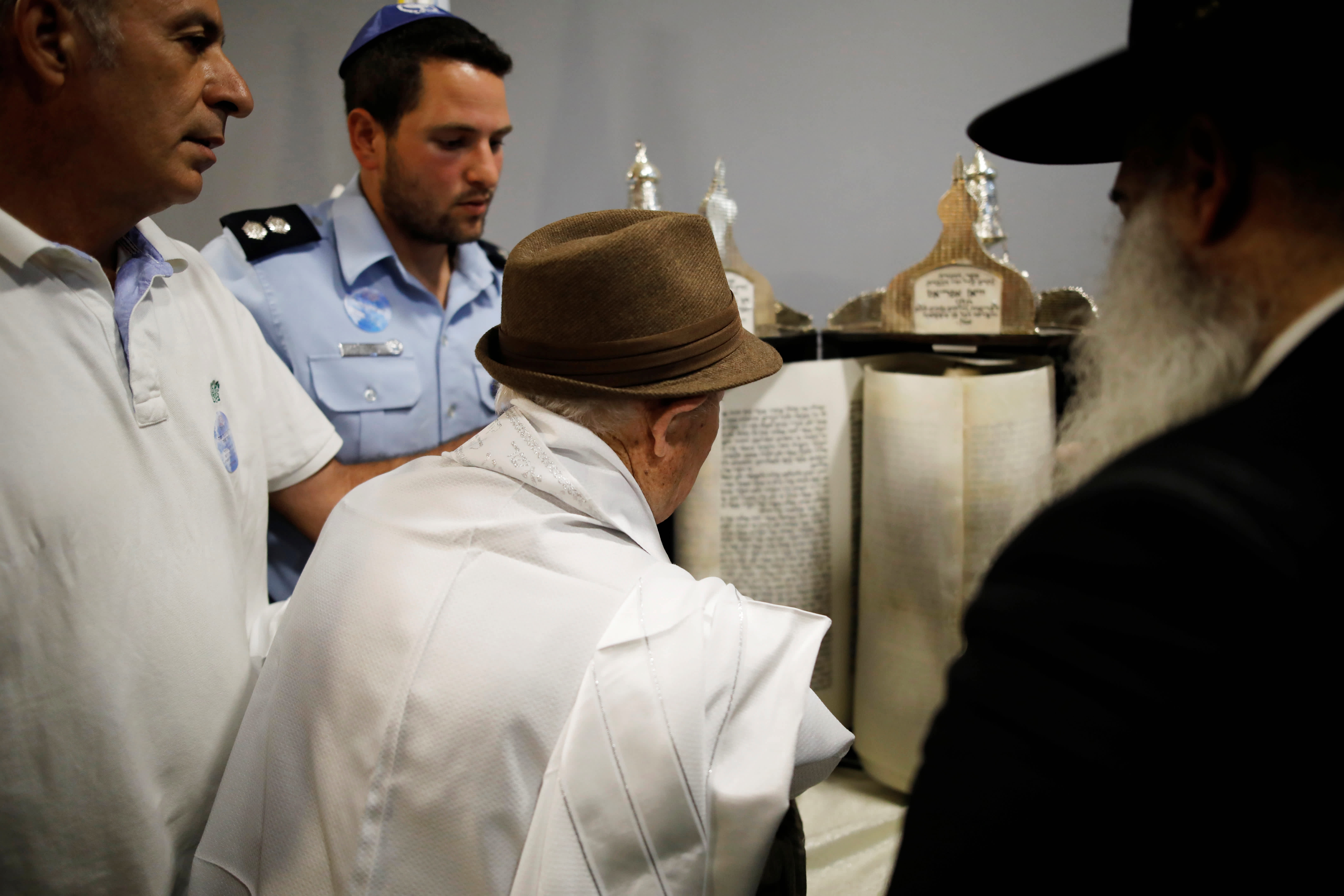 Shalom Shtamberg (C), a 93-year old Holocaust survivor, reads from a Torah scroll during his bar mitzvah ceremony, a Jewish coming-of-age celebration traditionally marked by boys at the age of 13, in Haifa, Israel August 31, 2017. (Reuters/Amir Cohen)