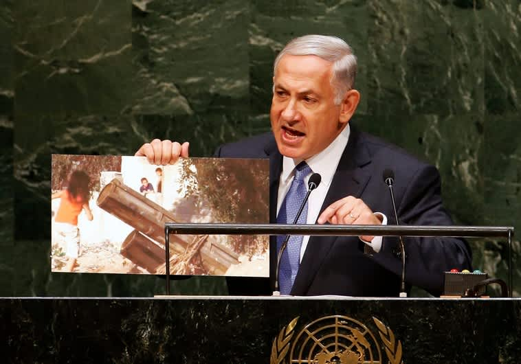 Israel's Prime Minister Benjamin Netanyahu holds up a photograph as he addresses the 69th United Nations General Assembly (Reuters)