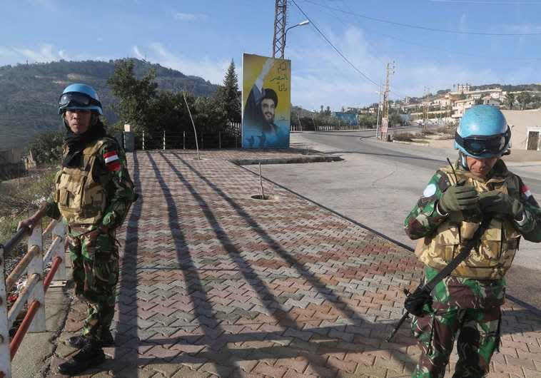 UNIFIL members beside a banner for Hezbollah leader Sayyed Hassan Nasrallah in south Lebanon (Reuters)