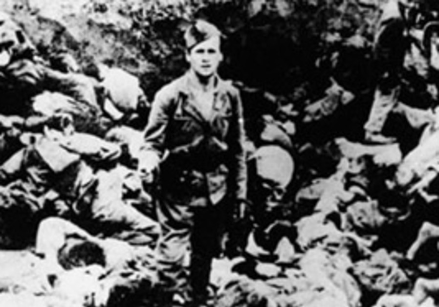 An Ustasha guard stands among the bodies of prison