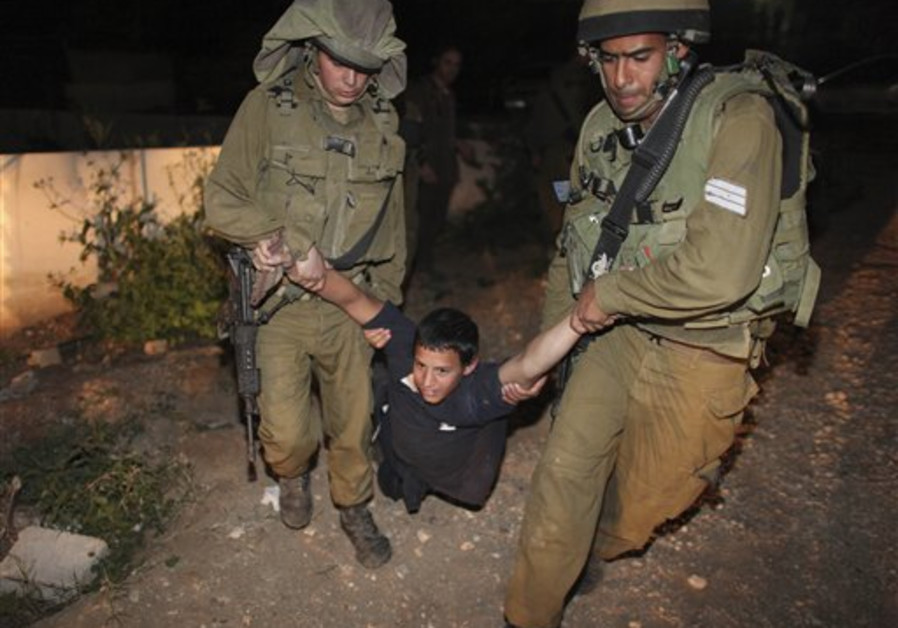 Israeli soldiers detain a Jewish settler after he