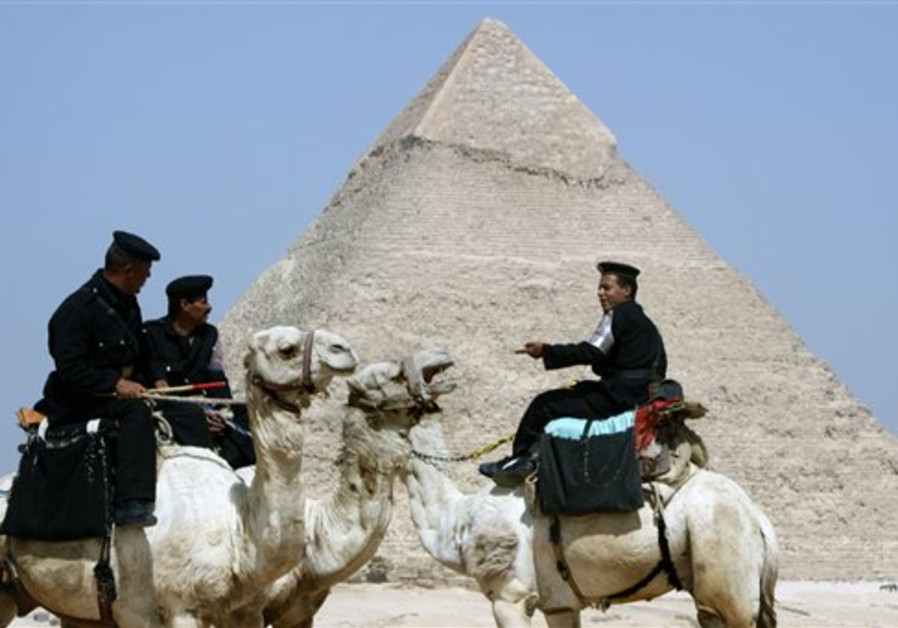 Egyptian tourism soldiers sit on their camels as t