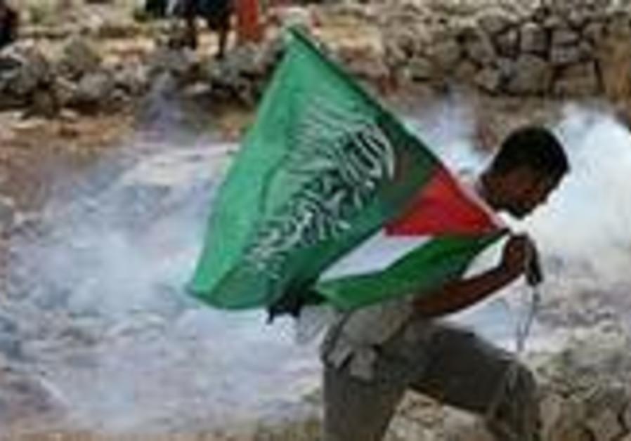 A Palestinian holds a green Islamic flag as he run
