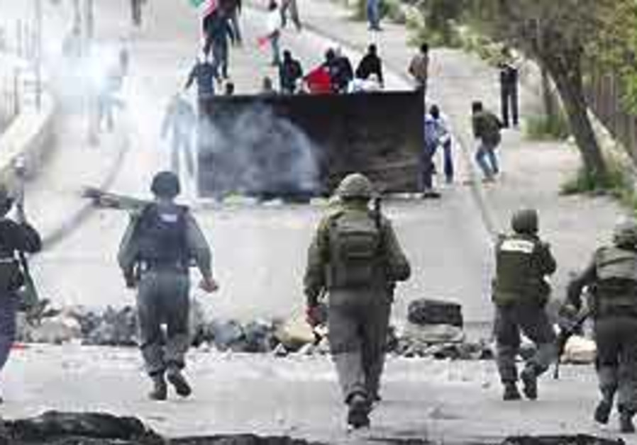 Police officers confront Palestinian rioters in th