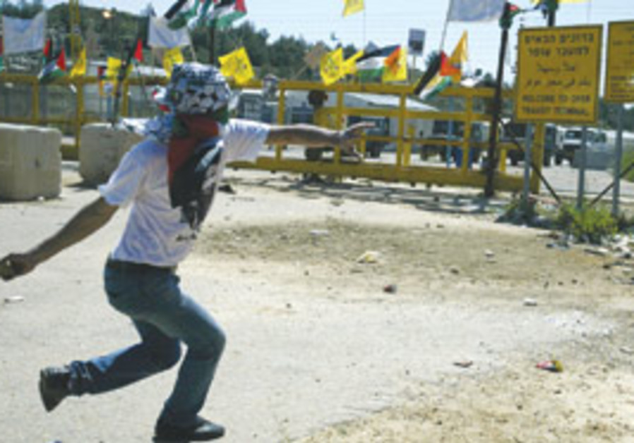 Palestinians throw stones at the Ofer Military Pri