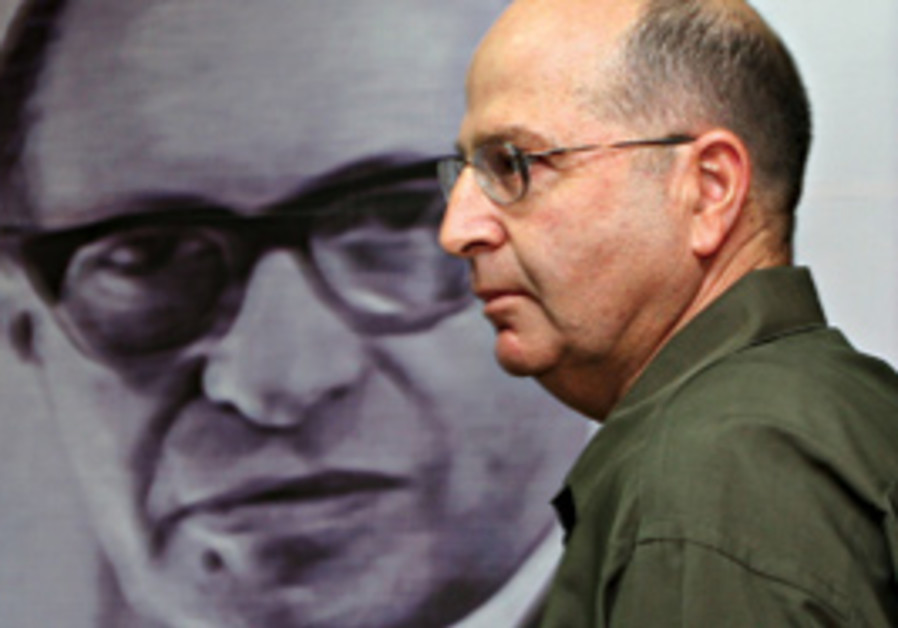 Ya'alon poses in front of a picture of Menachem Be