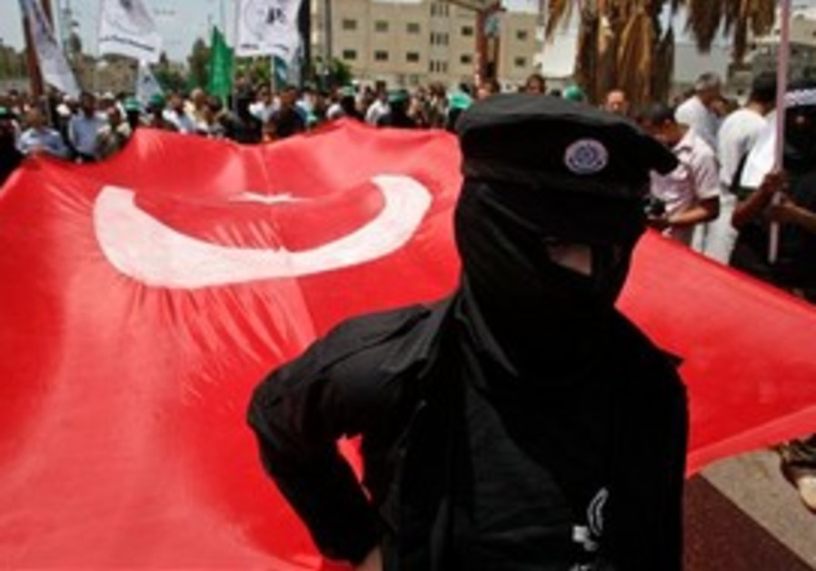 Masked Palestinian Hamas members hold up a Turkish