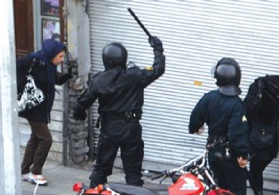 Repression: Iranian anti-riot police officers assault demonstrators during an anti-government protes
