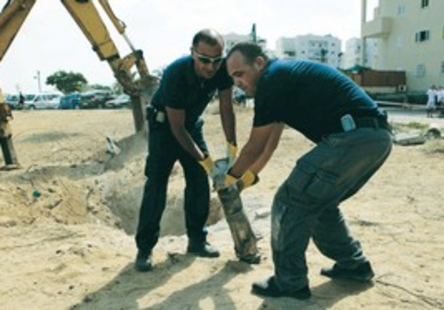 POLICEMEN REMOVE the remains of a Gazan rocket that hit Ashkelon on Friday.