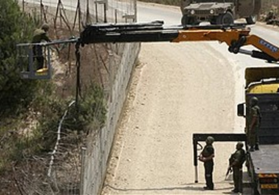 IDF soldiers use a crane to cut a tree on the Lebanese side of the border in the southern village o