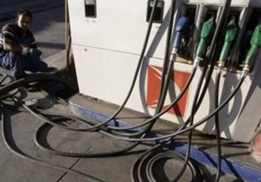 Worker filling a gasoline pump.