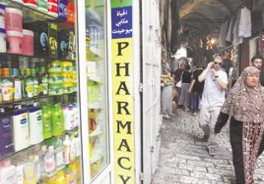 SHOPPERS WALK past a pharmacy in the Muslim Quarter in Jerusalem's Old City yesterday. If Ramadan fa
